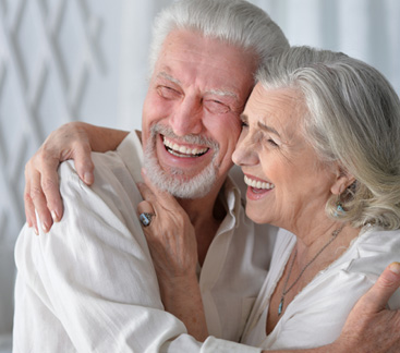Woman and man hugging and laughing